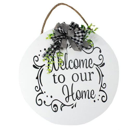 "White circle ""Welcome to our Home"" sign.  Black plaid bow with green stems at top hangs from rope.  Home, porch decor."