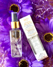Load image into Gallery viewer, Earth Lux Crystal Room Spray Displayed on Purple Flowers Showing the Bottle with Rose Quartz Crystals Inside.