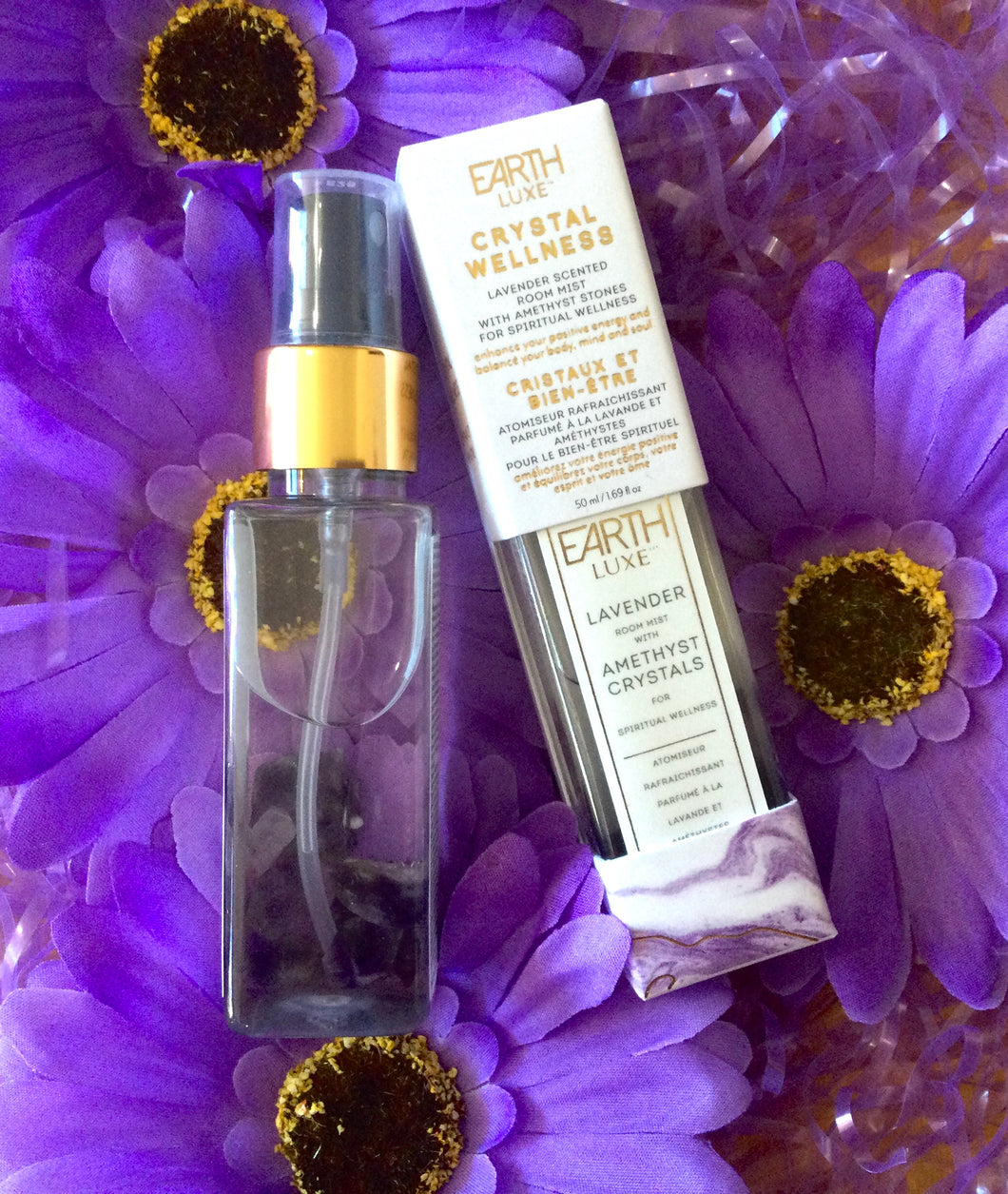 Bottle of Earth Lux Crystal Room Spray with Amethyst Crystals In Bottle Displayed on Purple Flowers.
