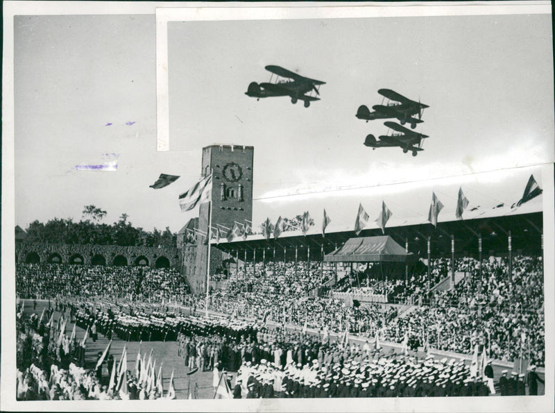 Swedish Flag Day - A group of military aircraft lands over packed Stadium - Reprint