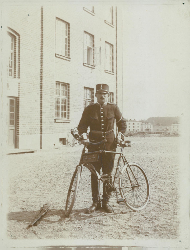 Man with bicycle at field operation. - Reprint