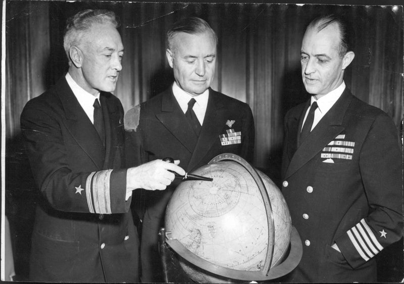 Sydpolsfararen Admiral Byrd discusses the globe Antarctic problems with a few employees, Admiral Forrest P. Sherman and Captain Richard H. Cruzen. - Reprint