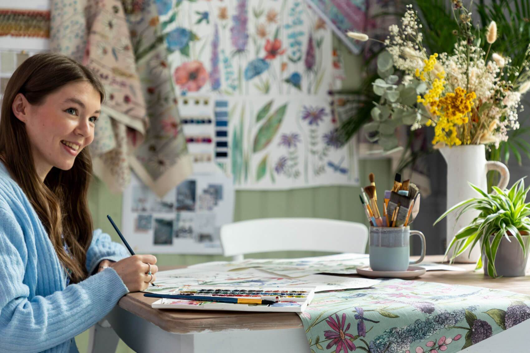 A textile designer in the studio painting a floral design from the new collection Florabunda