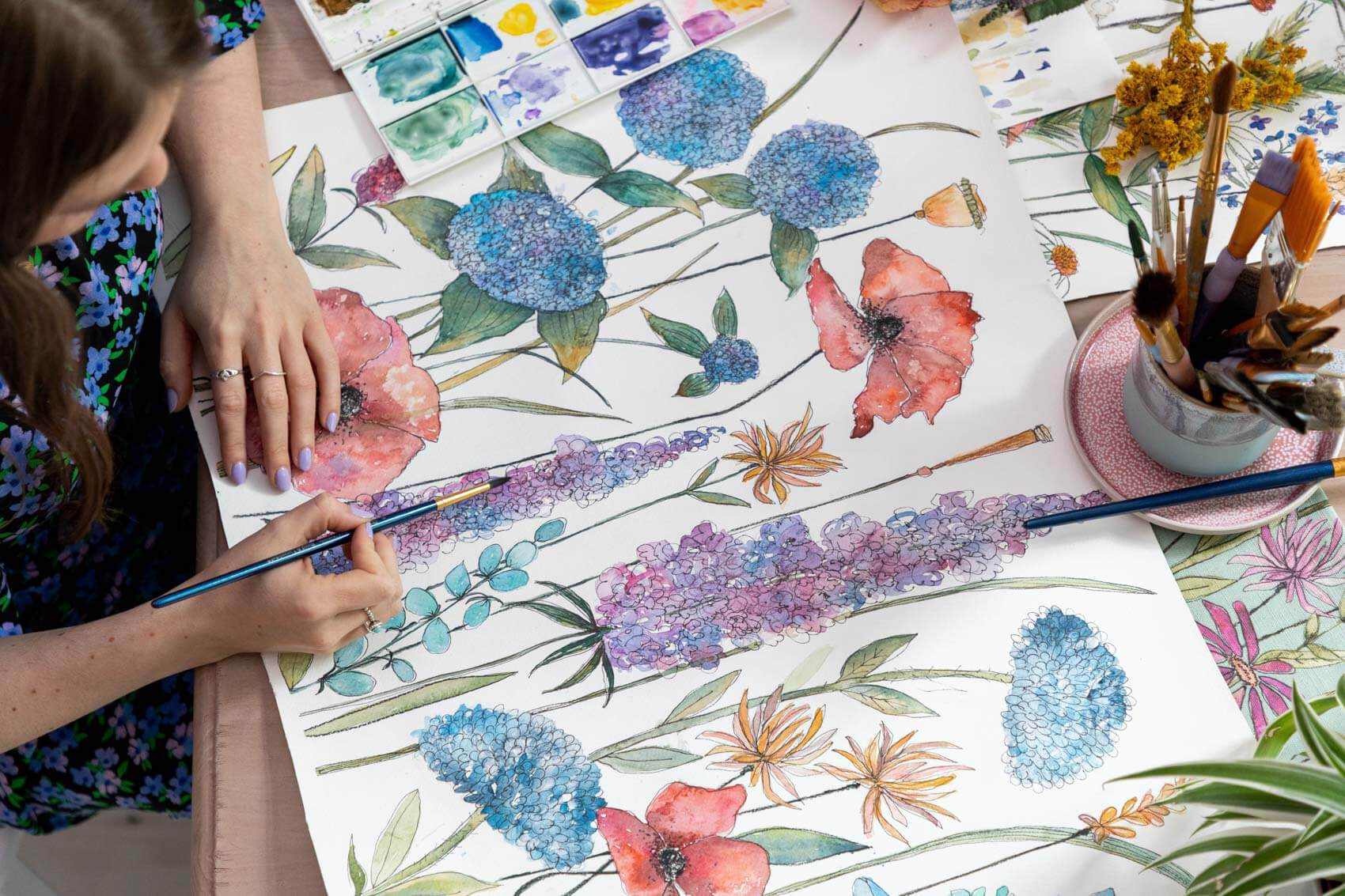 A textile designer painting a floral design from the new collection Florabunda