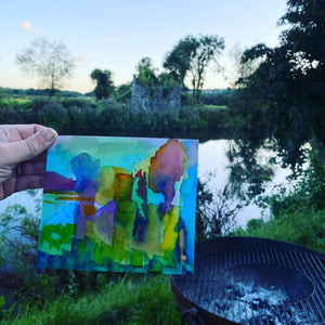 Abstrac5 watercolour sketch held out in front of a riverside landscape at sunset in the Wye Valley