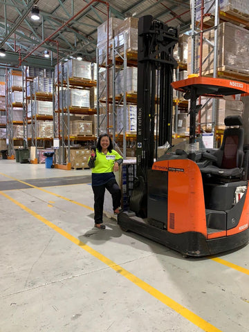 Pierlite staff member poses in front of a forklift