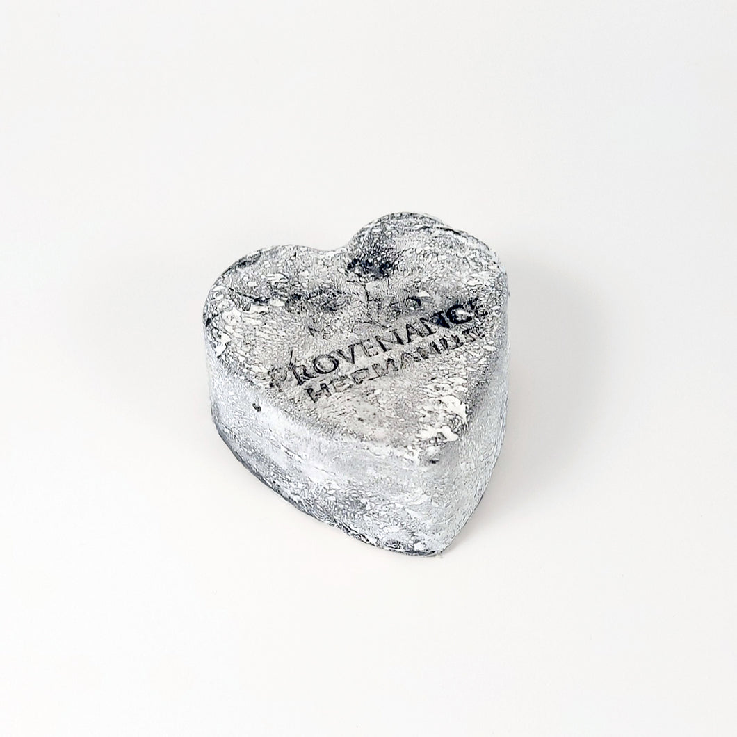 Handmade charcoal, heart-shaped soap bar with light coating of white powder.