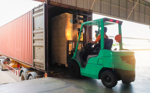 warehouse worker using forklift to put product on a shipping truck