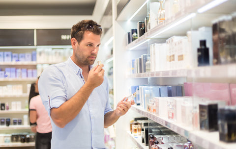 man smelling OTC beauty product while shopping
