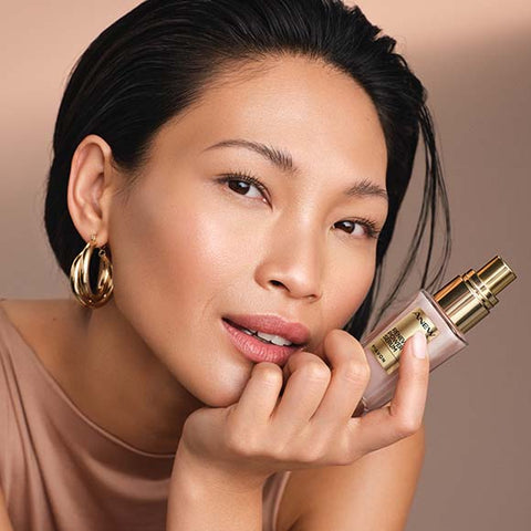 Model with gold earrings holding Anew Renewal Power Serum bottle.
