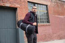 Load image into Gallery viewer, Male model standing with Black duffel bag with black and white checkered shoulder strap