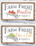 Two fall wood signs: one with peaches and one with corn in a wheelbarrow.