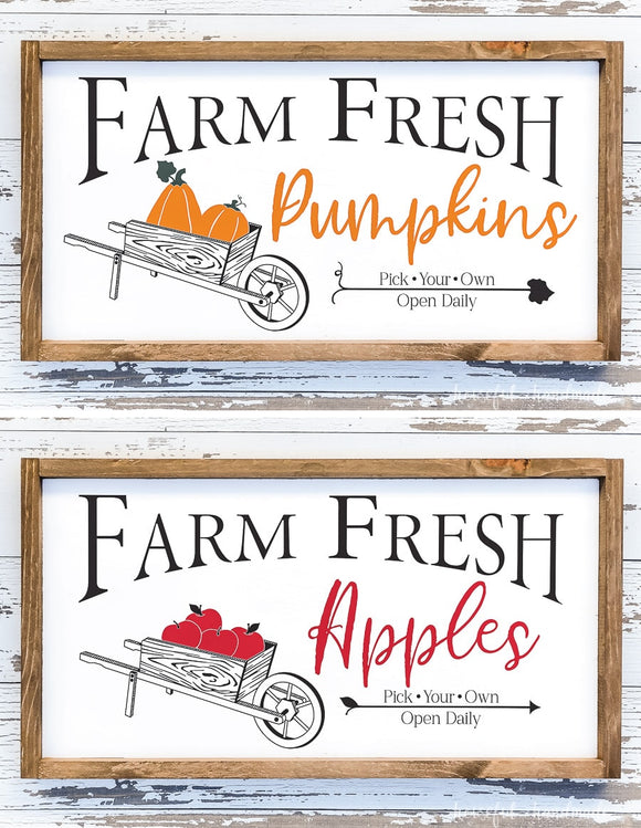 Farm fresh pumpkins and farm fresh apples signs with wheelbarrows full of produce.