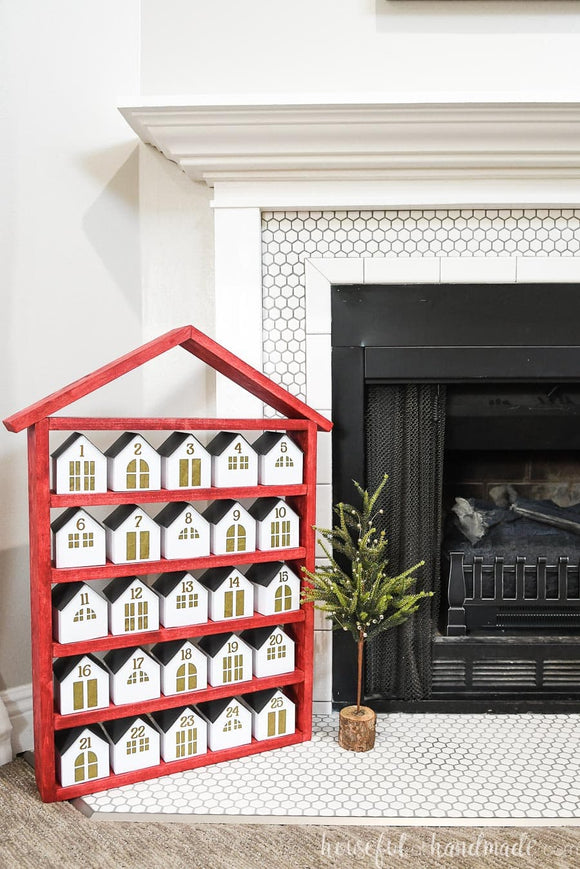 Red house shaped shelf with 25 paper houses as a DIY advent calendar.