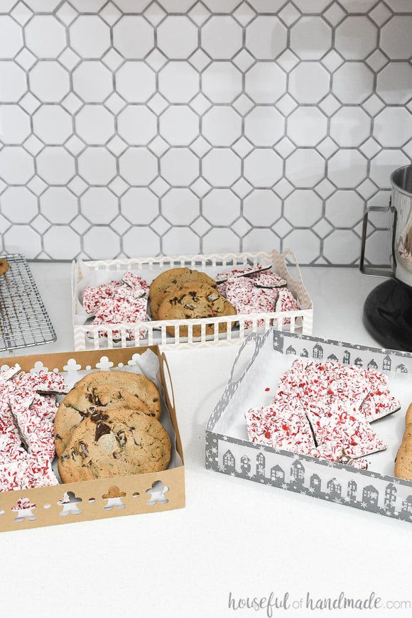 Three different designs on the sides of the paper trays filled with cookies and peppermint bark.