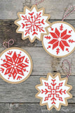 Four handmade Christmas ornaments with cross-stitched design on them.