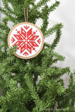Round cross-stitched paper ornament with Nordic snowflake design hanging on a tree.