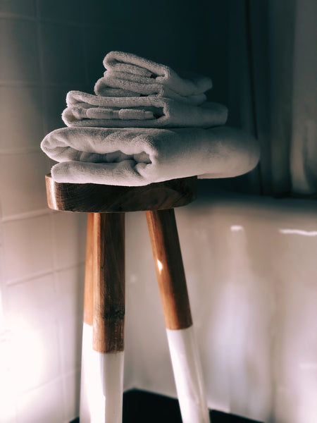 wooden bathroom stool with folded white towels on top
