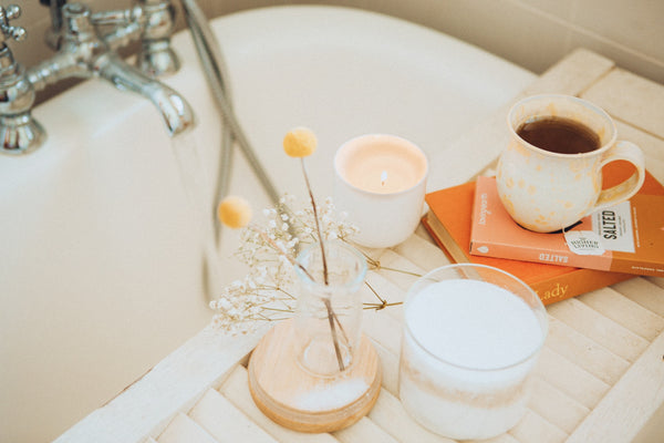 scented candle on white wooden bathtub caddy