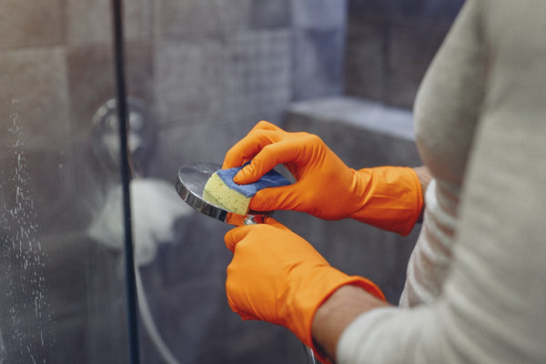 person wearing orange gloves cleaning back of shower head