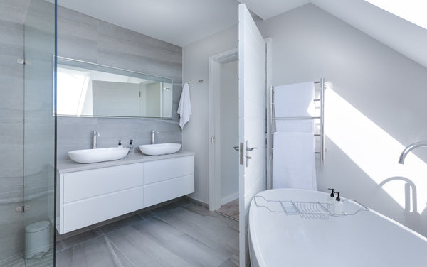bathroom with white bathroom fixtures and white tiles