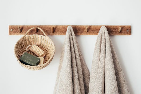two beige towels hanging from wooden hooks