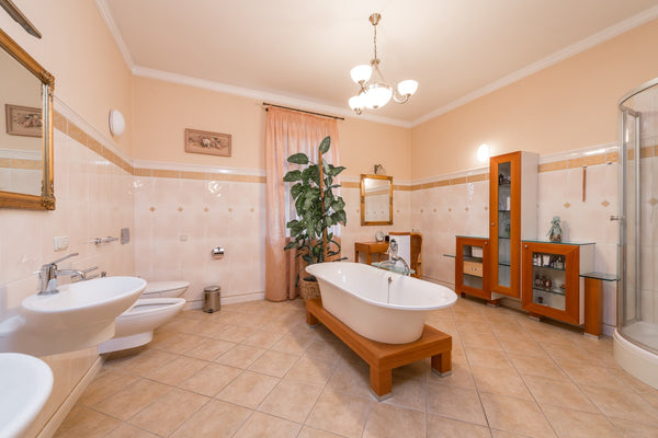 free standing tub in the middle of spacious bathroom with beige tiles
