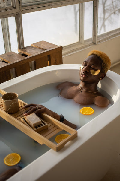 woman relaxing in a tub with the windows open to let natural light in