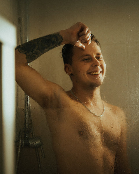 smiling man with tattoo inside the shower