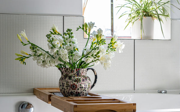 white flowering plant in a vase on top of wooden bathtub caddy