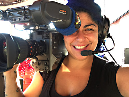 Kandi Sepulveda wearing a comms headset and carrying a hi-tech video camera.