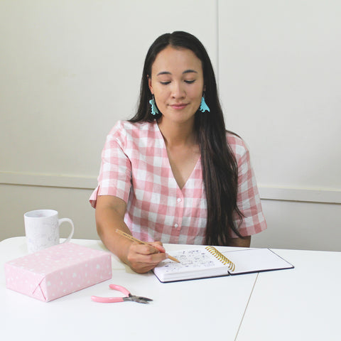 A maker at work. Adele has long dark brown hair and is wearing green T rex earrings and a pink and white gingham dress. She's sitting at a white desk, surrounded by tea cup, pliers and wrapped box. She's holding a pencil and sketching in her sketchbook.