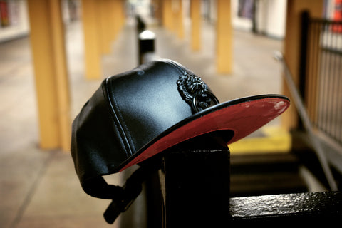 Red Bottom Black Faux Leather Cap with Large Black Metal Lion