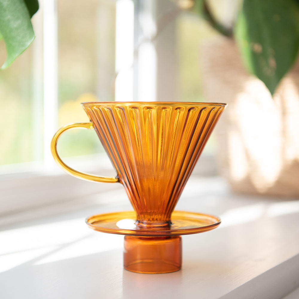 An amber glass v60 coffee dripper by Ordinary Better