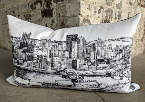 White pillow with Pittsburgh skyline printed on it. brick background