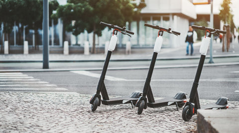 Three electric scooters parked side by side on the streed
