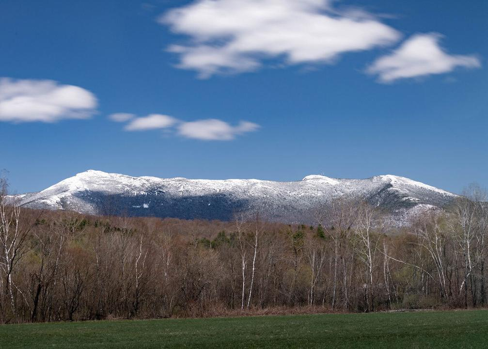 Spring photo of Mt. Mansfield, which has snow on its peaks. Green meadow in the foreground, the trees are just beginning to bud. Puffy clouds dot the vibrant blue sky.