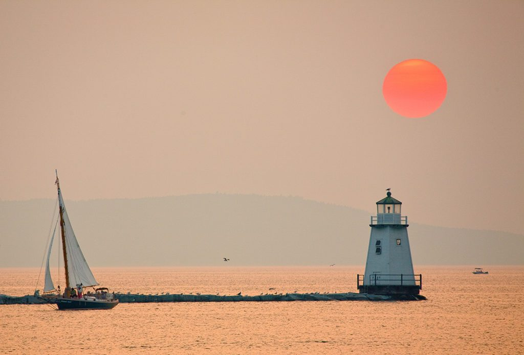 Sunset over Burlington Bay with breakwater lighthouse, red sun, and skiff