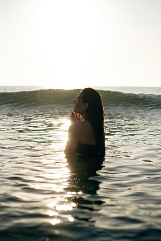 woman in water with hands near chest and sun glistening all around her