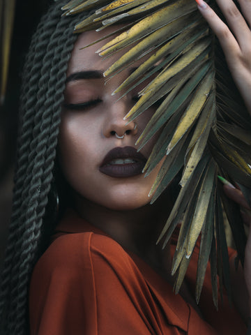 Multiracial woman with braids in her hair has a bush over her face and eyes closed.