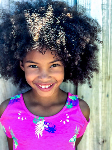 Multiracial child with super curly hair smiling in a very pink floral shit in-front of a door.