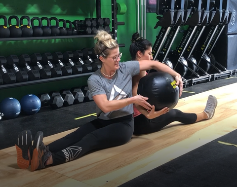 SoWal CrossFit® coach Rachael Tibesar warming up with one of our local members, passing the wall ball to activate the core.