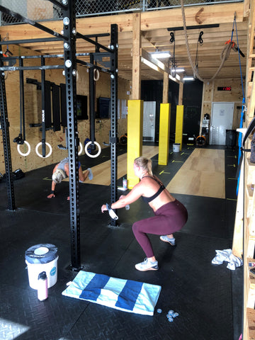 A SoWal CrossFit® athlete performing an air squat by the Rogue® Fitness monster rig