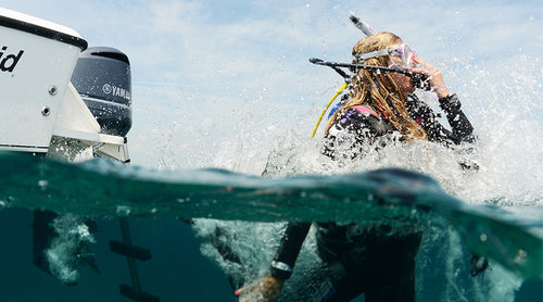 scuba diver surfacing away from the boat