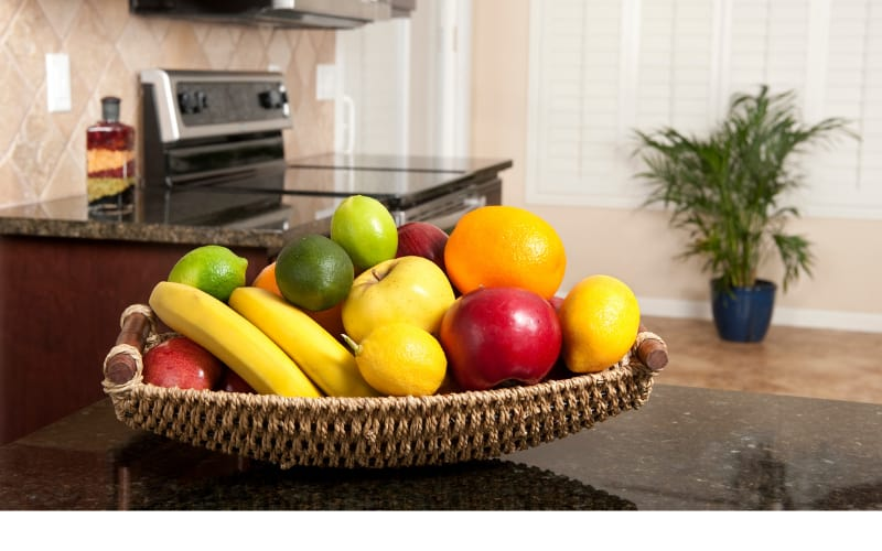 A basket of fruits placed on a countertop
