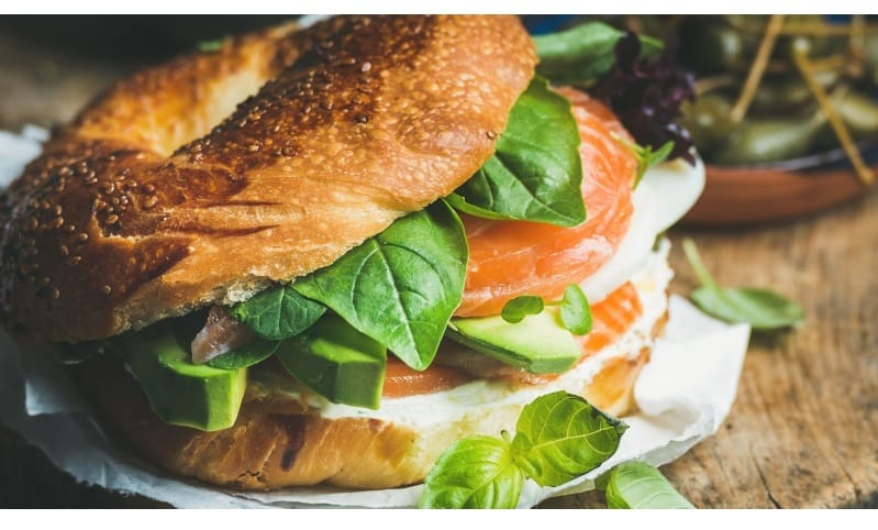 Smoked salmon bagel with basil leaves