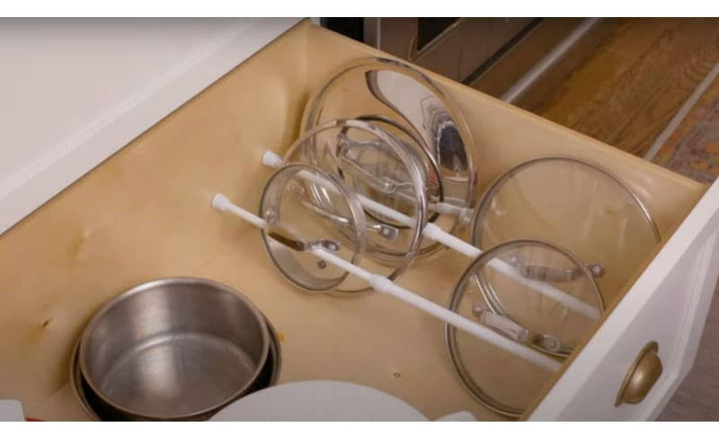 Tension rods being used to organize pot lids