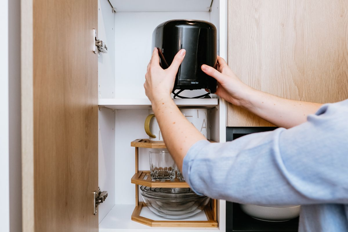A Man Putting a Toaster in the Cabinet