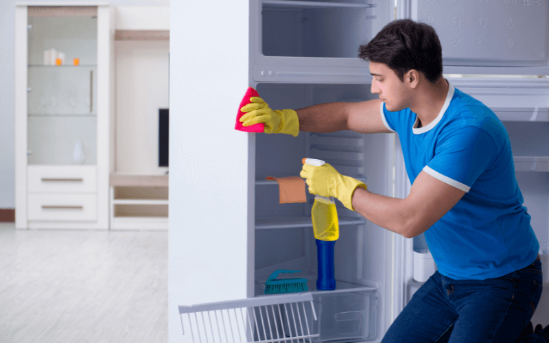 A man cleaning the fridge