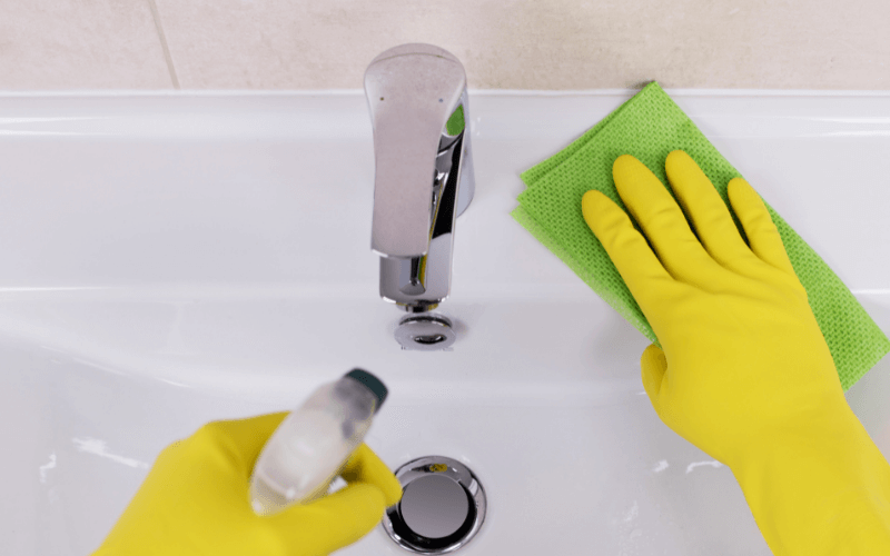 A person cleaning the sink with gloves and a microfiber towel